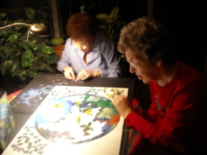 Mom in red building a puzzle at 88 with her friend, Judy.